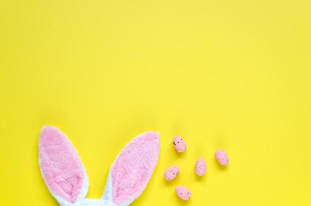 Pasen-vakantieachtergrond met konijntjesoren en paaseieren. kopieer ruimte achtergrond. plat leggen.