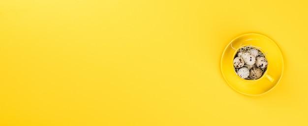 Pasen-vakantieconcept chequeeieren in een gele mok