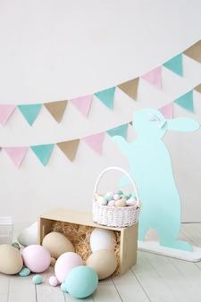 Pasen! veel kleurrijke paaseieren! pasen decoratie van een kamer met konijnen en manden met eieren. boerderij. oogsten. mand met wortelen en konijnen. pasen decor. vakantie vlaggen op witte muur