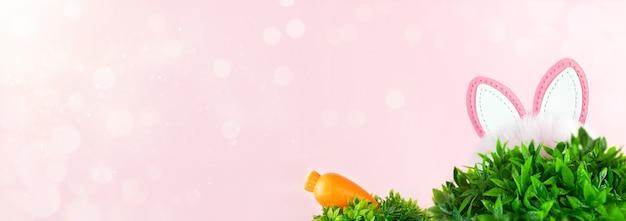 Pasen-verkoop met bunny's oren en wortel in gras op roze achtergrond.