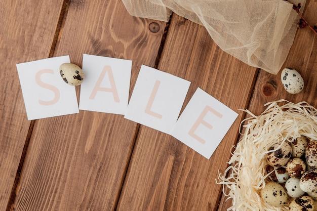 Pasen-verkoopbericht met paaseieren op een houten achtergrond