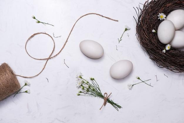 Pasen vieren in de lente. een nest met vijf witte paaseieren in huis.