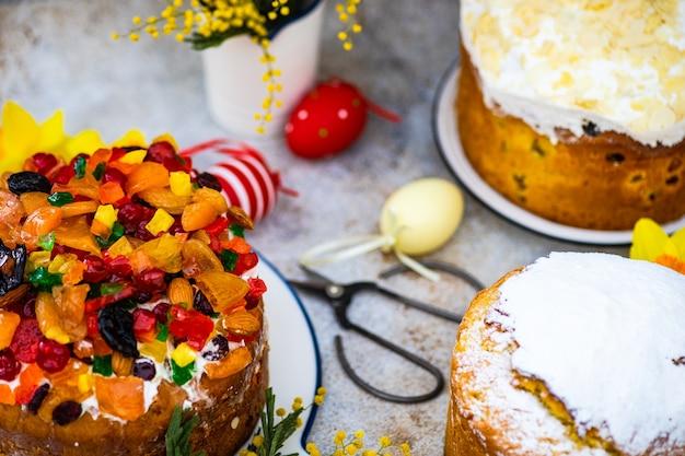 Pasen-voedselconcept met traditionele cake en gekleurde eieren die met lentebloemen worden verfraaid