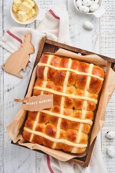 Pasen warme kruisbroodjes. traditioneel ontbijt en pasen bakken vakantie decoraties rabbiton witte houten achtergrond. heldere kleuren, van bovenaf bekijken op houten tafel.