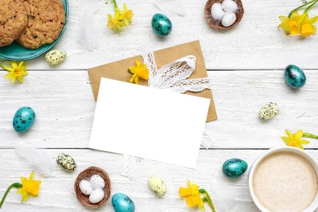 Pasen-wenskaart in frame gemaakt van kwarteleitjes, kopje cappuccino, lentebloemen en koekjes