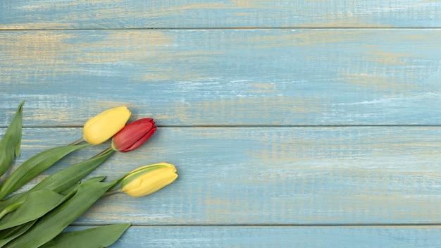 Pasen-wenskaart met de bloemen van de lentetulp over houten achtergrond. bovenaanzicht plat lag met kopie ruimte