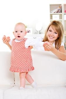 Pasgeboren baby begint te lopen met hulp van gelukkige moeder - thuis