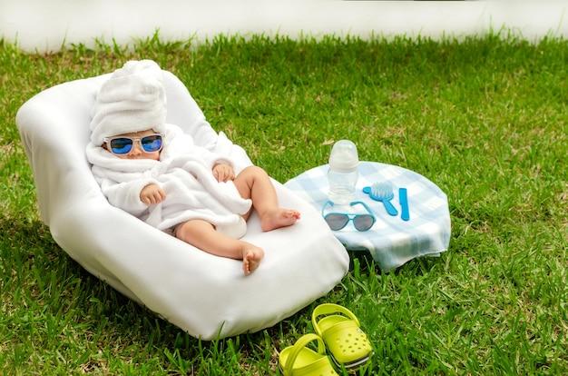 Pasgeboren baby bij outdoor spa-sessie rustende baby gekleed in badjas