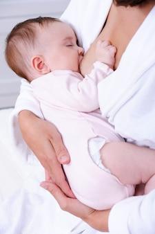 Pasgeboren baby die moedermelk zuigen