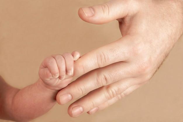 Pasgeboren baby die zijn hand op de vingers van ouders houdt