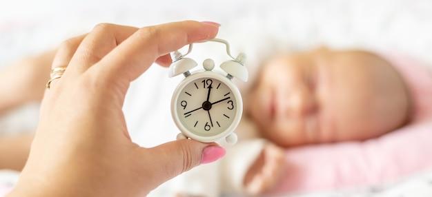 Pasgeboren baby en wekker. selectieve aandacht. mensen.