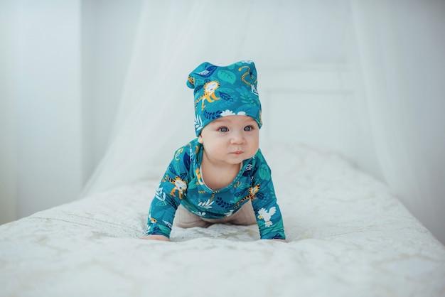 Pasgeboren baby gekleed in een groen pak liggend op een zacht bed