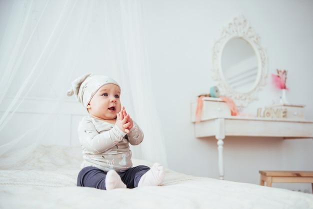 Pasgeboren baby gekleed in een pak op een zacht bed.