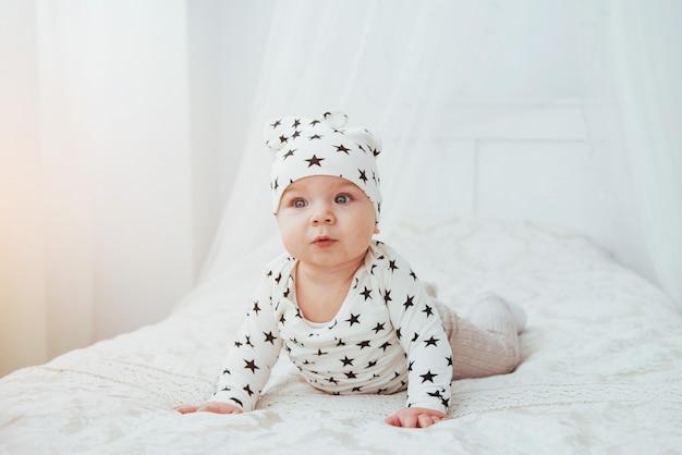 Pasgeboren baby gekleed in een wit pak en zwarte sterren is een wit zacht bed in de studio