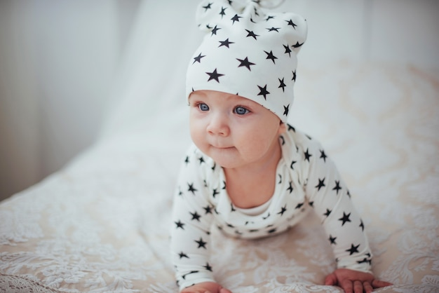 Pasgeboren baby gekleed in een wit pak en zwarte sterren is een wit zacht bed