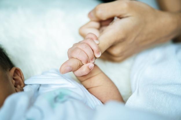 Pasgeboren baby hand in hand moeder