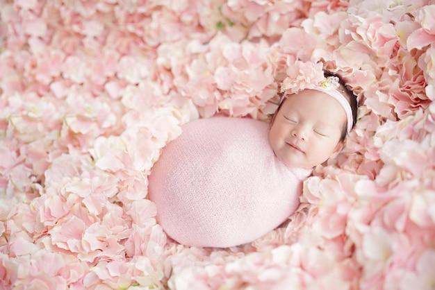 Pasgeboren baby heeft een zoete droom met een glimlach die een roze hoofdband draagt en een roze omslagdoek draagt die op veel roze hortensia's slaapt als een bloemenveld bovenop geschoten en de achtergrond geleidelijk vervaagd