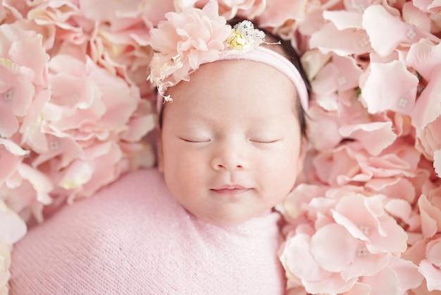 Pasgeboren baby heeft een zoete droom met een lieve glimlach met een roze bloemhoofdband en roze doeken klein meisje slaapt op roze hortensia's close-up shot