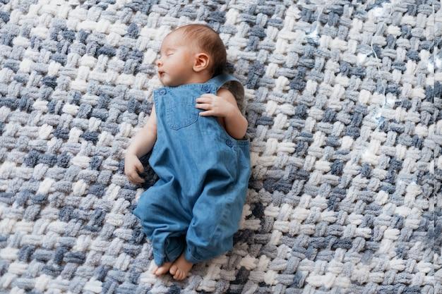 Pasgeboren baby in een blauwe jumpsuit liggend op een gebreide deken