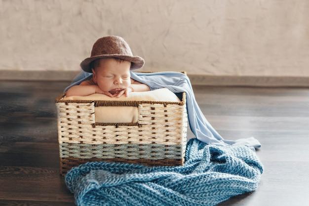 Pasgeboren baby in een hoed slaapt in een mand