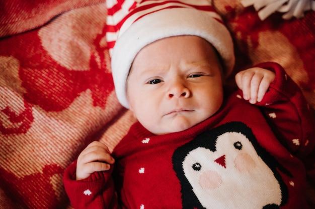 Pasgeboren baby in rood kerstkostuum