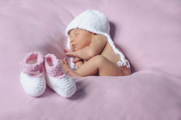 Pasgeboren baby in witte gebreide hoed en een paar baby witte en roze schoenen