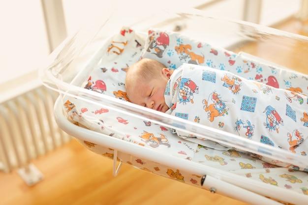 Pasgeboren baby in zijn babyjas in het ziekenhuis na de bevalling.