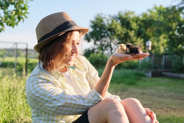 Pasgeboren baby kippen in de hand van boerin, rustieke stijl, landbouw, zonnige lentedag in de tuin