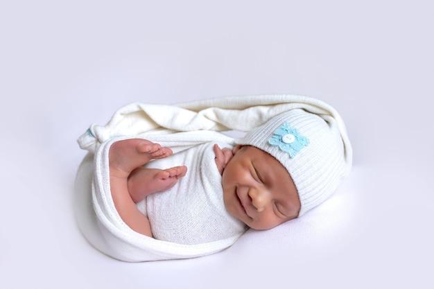 Pasgeboren baby lachend in een droom op een witte achtergrond in een slaapmuts