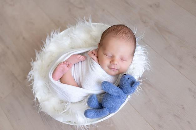 Pasgeboren baby lacht in zijn slaap en slaapt zoet in een coconluier met een teddybeerspeelgoed, gezonde babyslaap