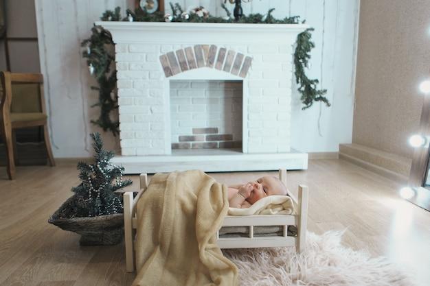 Pasgeboren baby liggend in een houten bed onder een deken