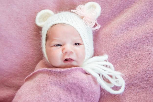 Pasgeboren baby liggend op een roze deken in een witte hoed met oren