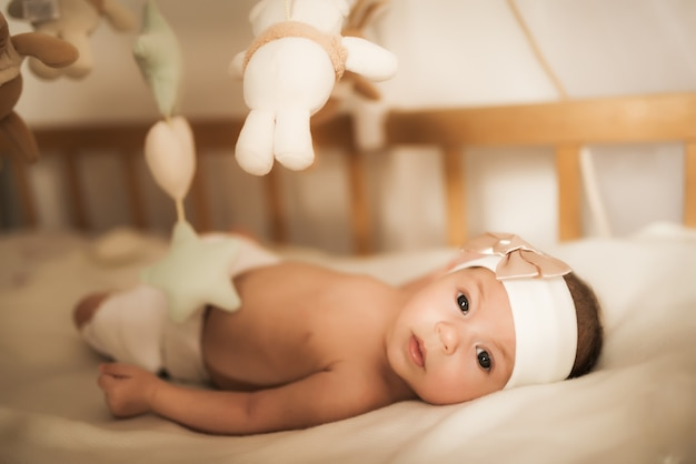 Pasgeboren baby ligt in de wieg onder speelgoed