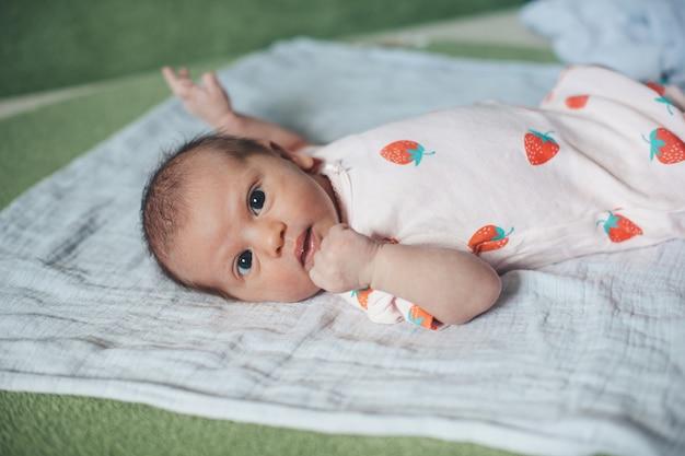 Pasgeboren baby met expressieve ogen ligt op een deken en kijkt naar de camera