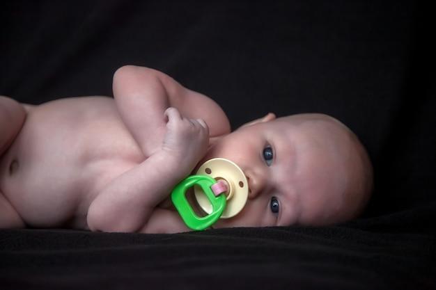 Pasgeboren baby met gekleurde fopspeen op donkere achtergrond. portret van een baby van een maand met blauwe ogen op de commode in de kamer. close-up van mooi kind op zwarte achtergrond. concept van nieuw leven