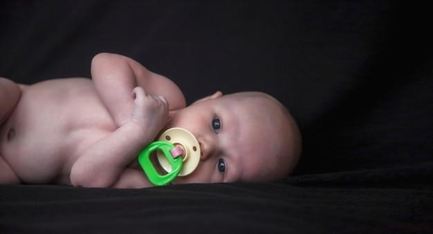 Pasgeboren baby met gekleurde fopspeen op donkere achtergrond