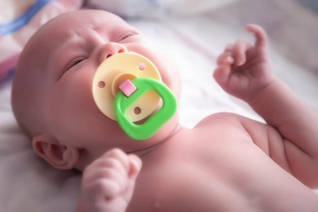 Pasgeboren baby met gekleurde fopspeen op wit bed