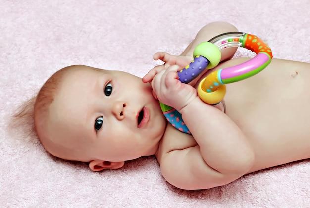 Pasgeboren baby met kleurrijke rammelaar