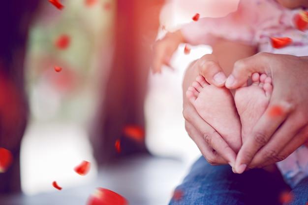 Pasgeboren baby's voeten en vaders handen houden hun voeten met liefde en zorg voor hun kinderen.