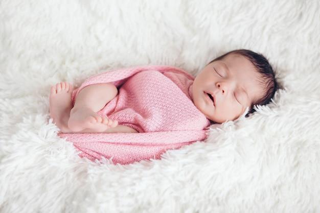 Pasgeboren baby slaapt gewikkeld in een deken.