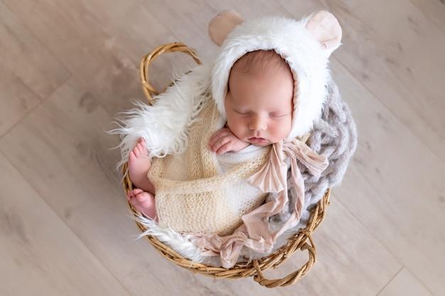 Pasgeboren baby slaapt heerlijk in een luier-cocon in een muts met berenoren, gezonde babyslaap