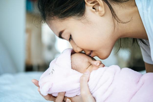 Pasgeboren baby slaapt in de armen van de moeder en geurig op het voorhoofd van de baby