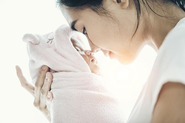 Pasgeboren baby slaapt in de handen van de moeder en de neus botste