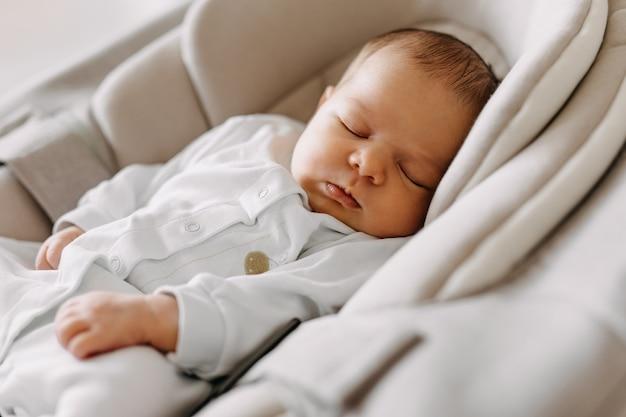 Pasgeboren baby slaapt in een schommel in een witte pyjama