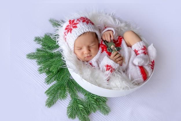 Pasgeboren baby slaapt in kerstaccessoires op een witte achtergrond, het concept van kerstmis en nieuwjaar