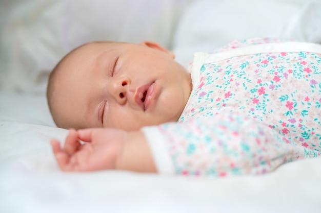Pasgeboren baby slaapt op een wit bed