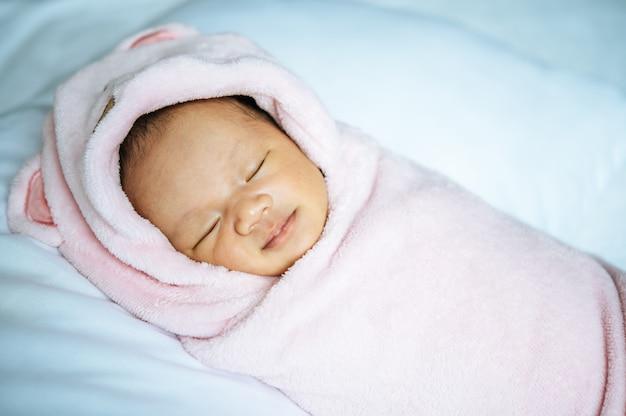 Pasgeboren baby slaapt op een zacht roze deken