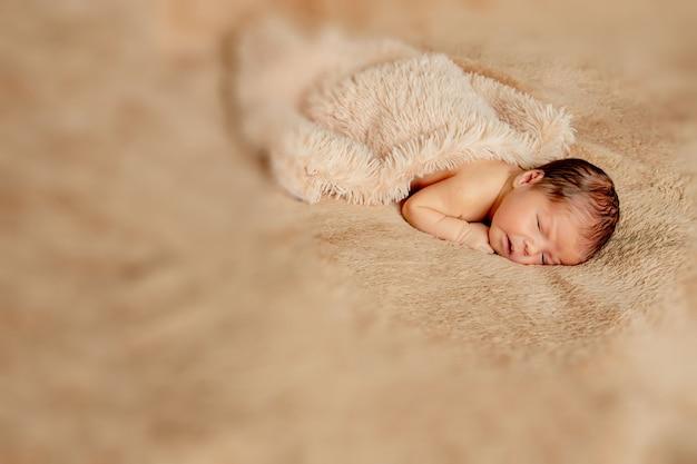Pasgeboren baby slaapt, rustend op haar eigen handen en ellebogen, op bruine achtergrond.