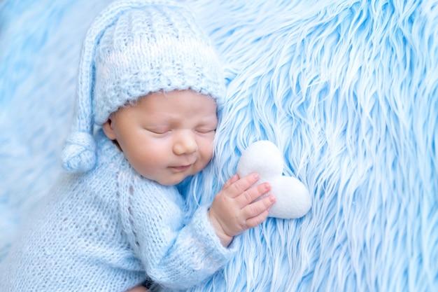 Pasgeboren baby slaapt zoet met een hartspeeltje in zijn hand, gezonde babyslaap