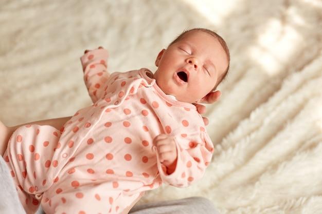 Pasgeboren baby slapen in de handen van de moeder, schattige jongen draagt slaper met polka dots, kind houdt mond geopend, klein meisje in mama's armen op achtergrond van witte pluizige deken.